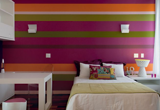 O grande destaque desse quarto é pintura listrada na parede do fundo. O pink foi quebrado com lilás, laranja e verde, com um efeito feminino e moderno ao mesmo tempo. Os móveis são todos em laca branca, criando um bonito contraste com a parede, e o espaço dos estudos foi priorizado pela posição da escrivaninha. Foto: Casa e Jardim.