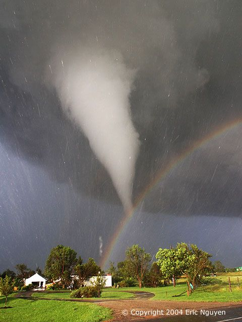 Tornade naissante sous un angle inhabituel, celui d'un arc-en-ciel. Sur la photo, une tornade blanche descend d'un nuage dorage sombre. Le Soleil, perçant à travers un morceau du ciel dégagé sur la gauche, illumine des maisons à l'arrière-plan. La lumière du Soleil se réfléchit sur les gouttes de pluie pour former un arc-en-ciel. Par hasard, la tornade semble finir juste au-dessus de l'arc-en-ciel. Les traînées dans l'image sont de la grêle balayée par les vents tourbillonnants.