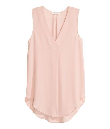 Powder pink. CONSCIOUS. Gently flared, sleeveless blouse in airy crêpe. V-neck with a pleat at center front and rounded hem. Slightly longer at back. Made