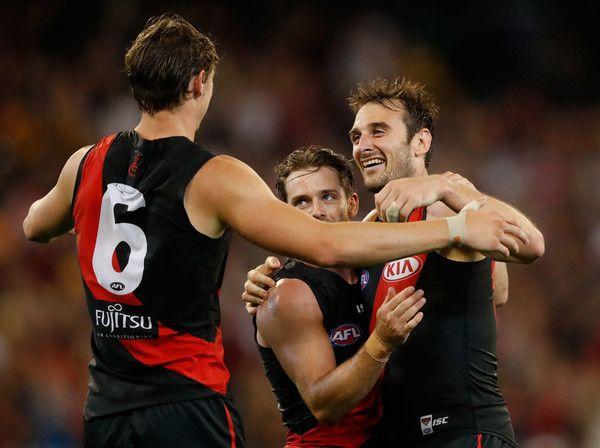 Jobe Watson of the Bombers (right) celebrates on the final siren with Travis Colyer and Joe Daniher (left) of the Bombers during the 2017 AFL round 01 match between the Essendon Bombers and the Hawthorn Hawks at the Melbourne Cricket Ground on March 25, 2017 in Melbourne, Australia.