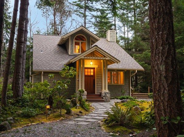 small house in woods with warm glow from front door