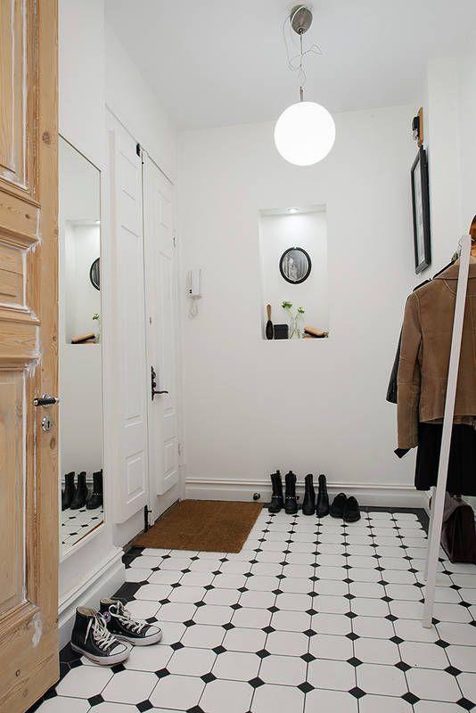 Nowoczesne sprzęty – lustro w białej prostej oprawie i wolno stojący wieszak – pozostają w cieniu pięknej klasycznej posadzki. Ściany zdobią obraz zawieszony naprzeciw wejścia i podświetlana nisza w ścianie. Pod owalnym obrazkiem wyeksponowano w niej przekornie akcesoria do czyszczenia butów.