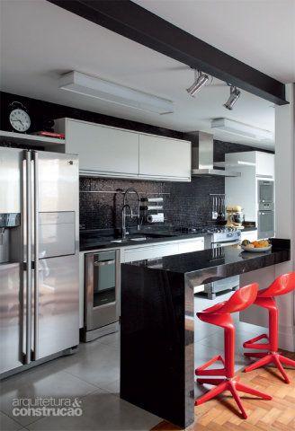 A cozinha com bancada de granito preto São Gabriel, cresceu ao avançar quintal afora e emendar na antiga edícula. Exibe uma das quatro vigas aparentes e pintadas de preto da obra. Projeto de Luciana Galves Arquitetura.