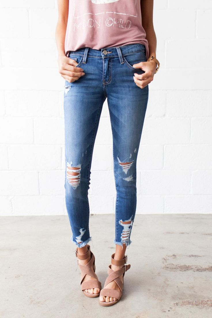 Our Smooth Move Cropped Flying Monkey Skinnies feature a standard 5 pocket style, front button enclosure, and a medium wash denim, knee distressing, frayed hem, shin distressing, and gold stitching. -
