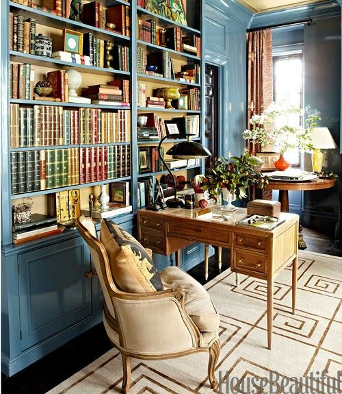 """The library in designer Garrow Kedigian's Manhattan apartment sheds fresh light on the classics he collects, both literary and decorative. A bergère in Pierre Frey's Dune partners with a mid-20th-century inlaid desk. Custom Stark rug with the designer's hallmark Greek key pattern."" Interior design by Garrow Kedigian. Photography by Christopher Sturman. ""A Stylish Spin on a Traditional New York Apartment"" by Douglas Brenner. House Beautiful (December 2013)."