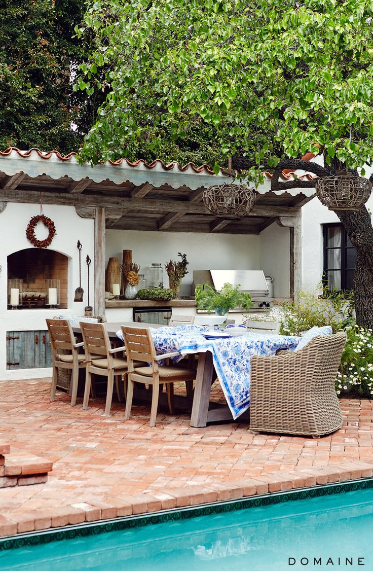 Backyard dining area with blue and white tablecloth Más
