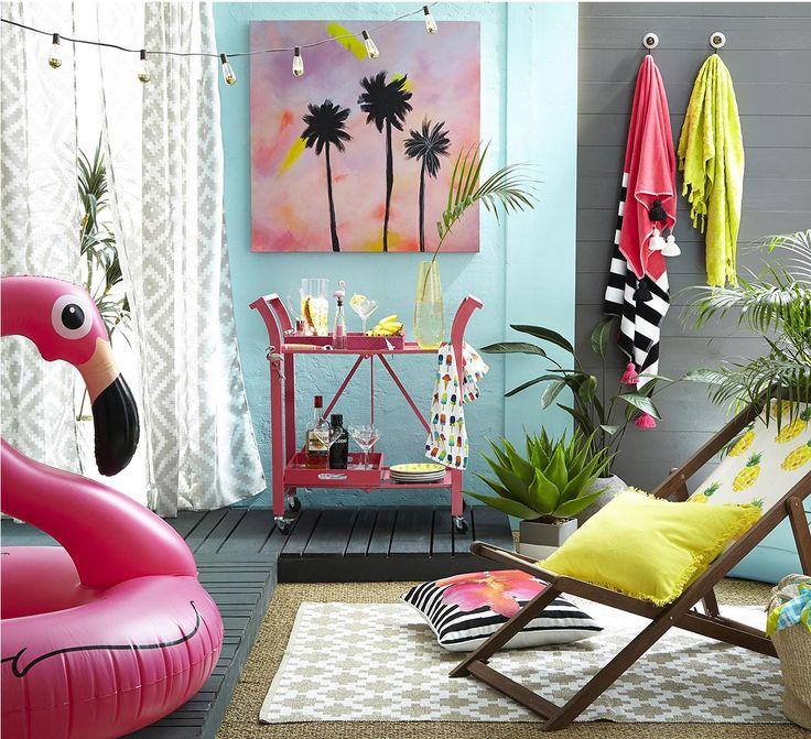 Inspirations déco d'été ; un flotteur de piscine en forme de flamant rose une chaise sling à motif d'ananas un chariot de service de bar rose et des coussins d'extérieur.