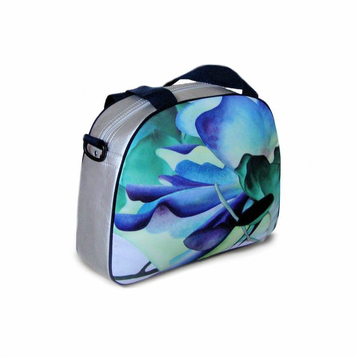 """Artbag """"Blues"""" displays Dutch floral art on outdoor textile on one side of the bag. Shoulder bag with detachable handles, zipper inside. Four studs on the bottom of the bag help it stand upright. Silver-coloured artificial leather, with dark blue hand- and shoulder straps. Price: 60 euro excl transport costs. Order via info@florifique.com."""