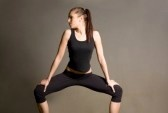 Yoga : Slender fit young brunette in yoga squat pose. Stock Photo