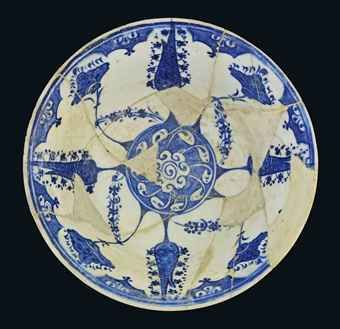 AN IZNIK BLUE AND WHITE POTTERY BOWL OTTOMAN TURKEY, CIRCA 1520  interior decorated with a central roundel containing a flowerhead issuing swirling leaves reserved against cobalt-blue ground, the cavetto with a series of alternating cypress trees issuing small rosettes and lotus blossoms on long swaying branches, four diagonal sprigs of hyacinth blossoms join them, the rim with small cusped panels with trilobed motifs, the exterior with staggered rows of large rosettes and trilobed motifs