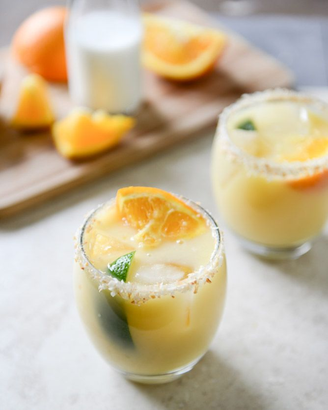 Coconut Creamsicle Margaritas  2 ounces grand marnier 2 ounces orange juice 1 1/2 ounces silver tequila 1 ounce lime juice 1 ounce coconut water 1 ounce canned light coconut milk 1 ounce simple syrup unsweetened shredded + toasted coconut for glass rims orange + lime slices for serving
