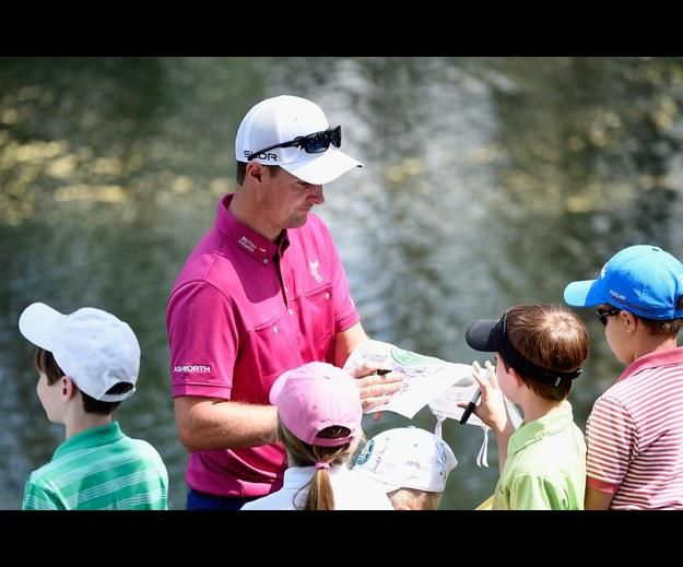 The Masters - Preview Day 3 AUGUSTA, GA - APRIL 09: Justin Rose of England signs his autrograph for young patrons during the 2014 Par 3 Contest prior to the start of the 2014 Masters Tournament at Augusta National Golf Club on April 9, 2014 in Augusta, Georgia. Credit: Harry How/Getty Images Date: Apr 09, 2014