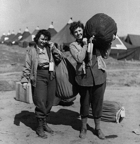 Two US army nurses carry their barracks bags to their quarters after arriving recently at an Anzio beachhead hospital. Left to right are: Maxine L. Burton, of Kearney, NE., and Lt. Jean Heaslip of Youngstown, Ohio. 10 April 1944, Italy ~