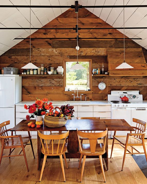 """Yianni Doulis and Jessica Helgerson covered many walls in their cottage in wood cladding reclaimed from a barn on the property. """"We stained one wall and painted the rest white -- it was just too much to have natural wood everywhere,"""" says Helgerson. They used metal collar ties instead of wooden joists along the ceiling to create a sense of openness."""