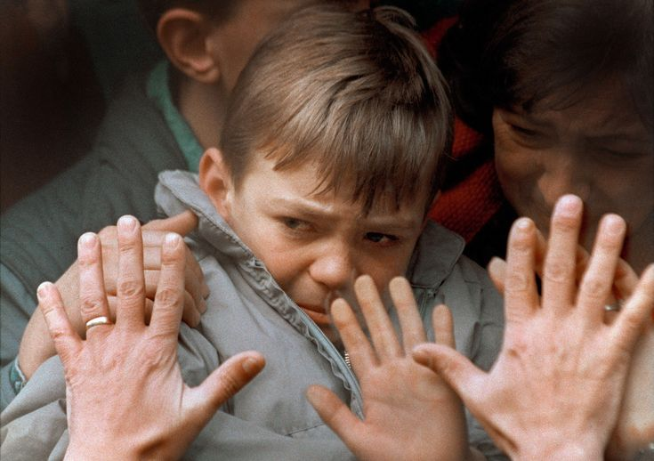 A father's hands press against the window of a bus carrying his tearful son and wife to safety during the Siege of Sarajevo, November 10, 1992 -