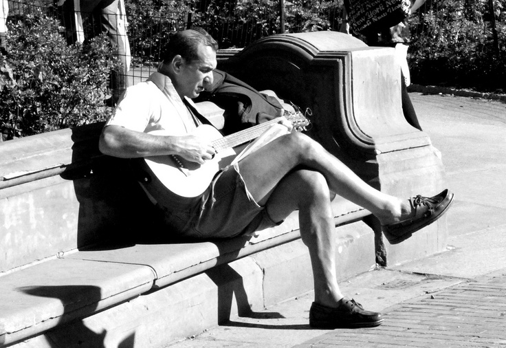 Man playing his guitar in Central Park.