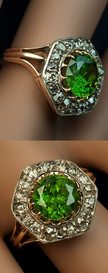 A Rare Almost 3 Carat Russian Demantoid and Diamond Ring  made between 1908 and 1917  The silver topped 14K gold ring features a very large vivid grass green 2.84 ct Russian demantoid (8.55 x 5.45 mm) prong-set in gold   within a hexagonal frame embellished with old cut diamonds (approximately 1.20 ct total weight).  Marked with 56 zolotnik gold standard