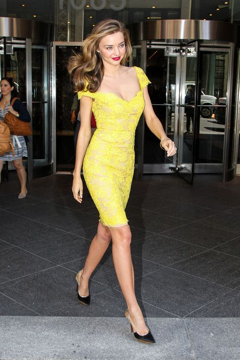 Miranda Kerr in a beautiful bright yellow lace dress and black pumps.