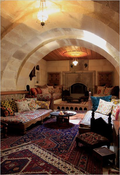 a home in Turkey built in a series of caves. love the low benches piled  with cushions, the rugs on the floor, and the fireplace/stove at the heart  of the ...