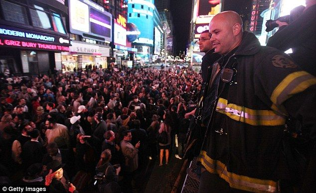 FDNY firefighter Aaron Clark looks on from atop a firetruck as people celebrate in Times Square after the death of accused 9/11 mastermind Osama bin Laden