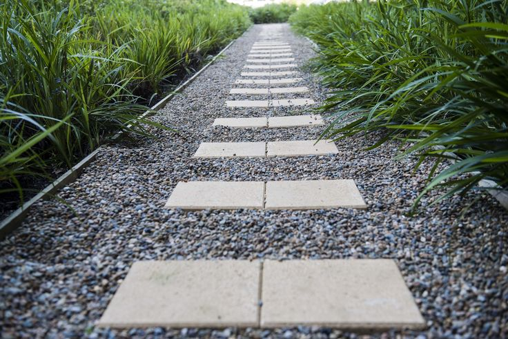 Secret garden pathway with stepping stones in gravel surrounded by lush planting of native grasses.