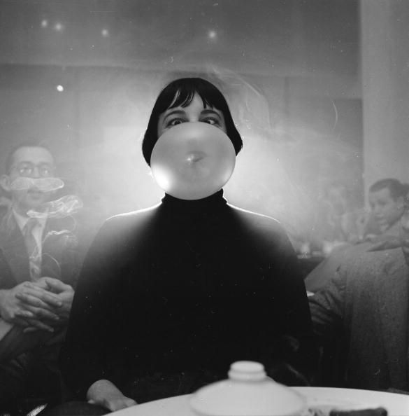 1940: A woman in a nightclub goes cross-eyed as her bubblegum bubble expands in front of her face. (Photo by Weegee(Arthur Fellig)/International Center of Photography)