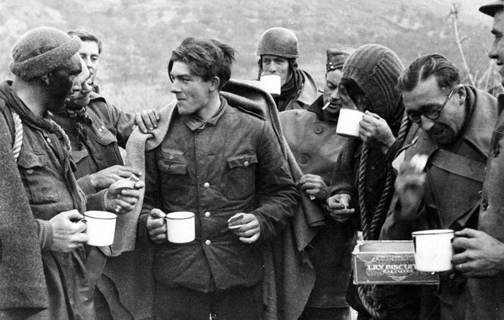 British Commandos share tea and biscuits with an German prisoner which they captured during a raid, 1944.