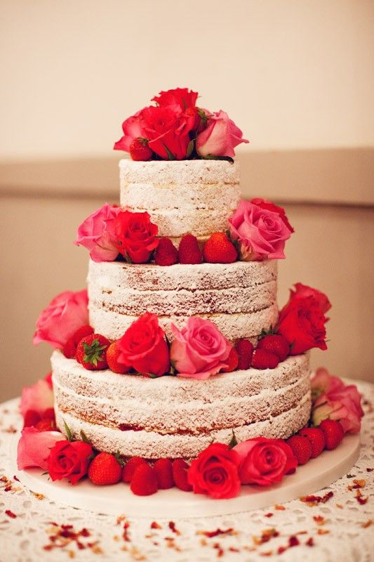 This is a traditional naked cake, icing sugar dusted and decorated with strawberries and fresh roses. Absolutely beautiful!
