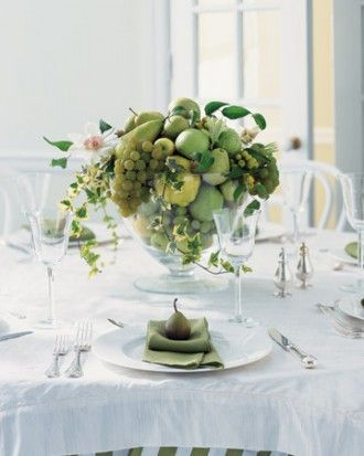 This clear glass footed bowl is overflowing with fresh green fruit -- quince, grapes, Anjou pears, apples, and chinaberries -- and delicate flowers. Variegated ivy and white blooming clematis vines form graceful twirls around the mount of fruit.