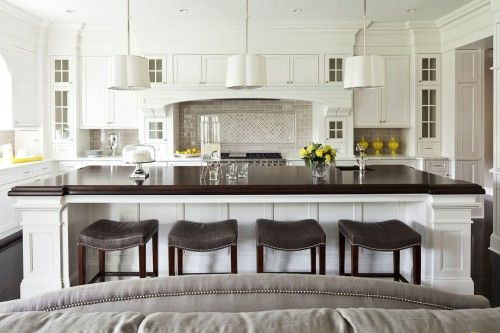 White kitchen with large island, glass cabinets