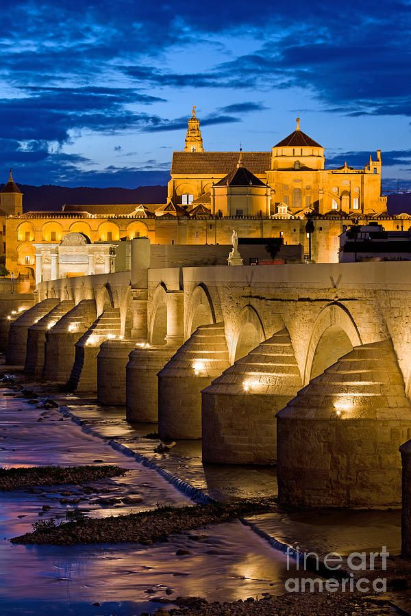 Roman Bridge on Guadalquivir river and Mezquita Cathedral at twilight in Cordoba, Spain