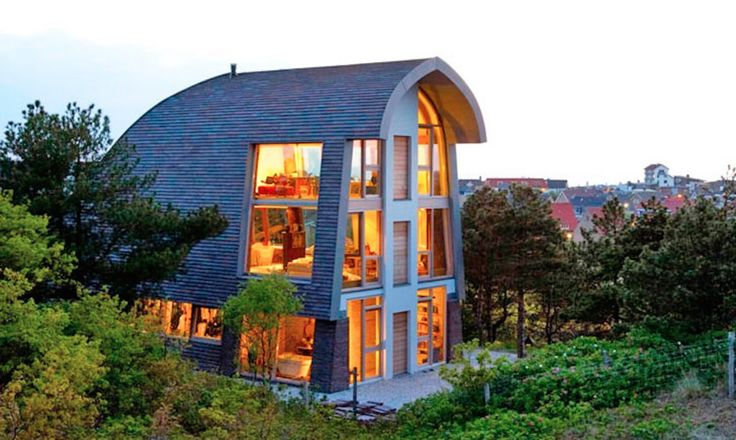 Min2's Dune House dramatically rises out of a coastal dune crest in North Holland. Designed to match the vernacular of the surrounding landscape, the three-story house and studio echoes the shape of a dune or a windswept group of trees. Fitting into an undulating landscape, the Dune House also explores a reinterpretation of the traditional Dutch farmhouse with a modern and sustainable twist.