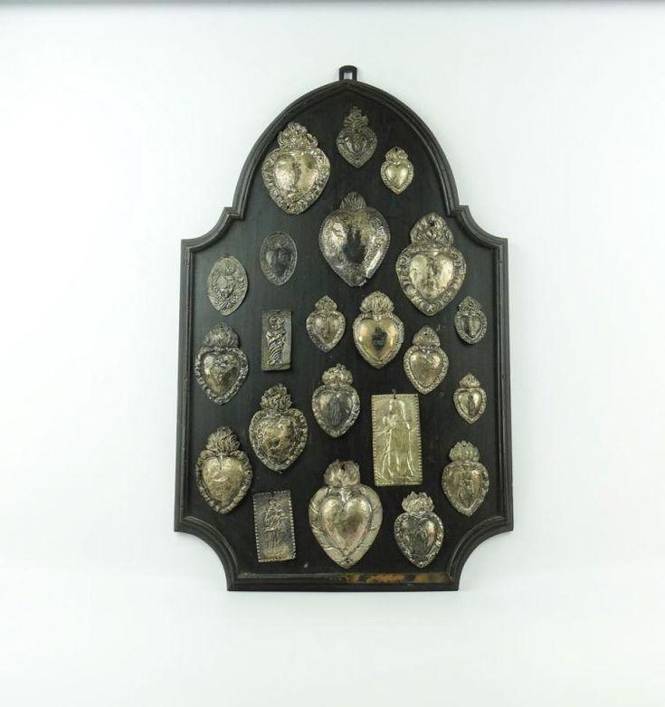 Lot 3473 - schild met ex voto gezwart houten schild met zilveren ex-voto schilden, 18e en 19e eeuw, h. 76 cm.