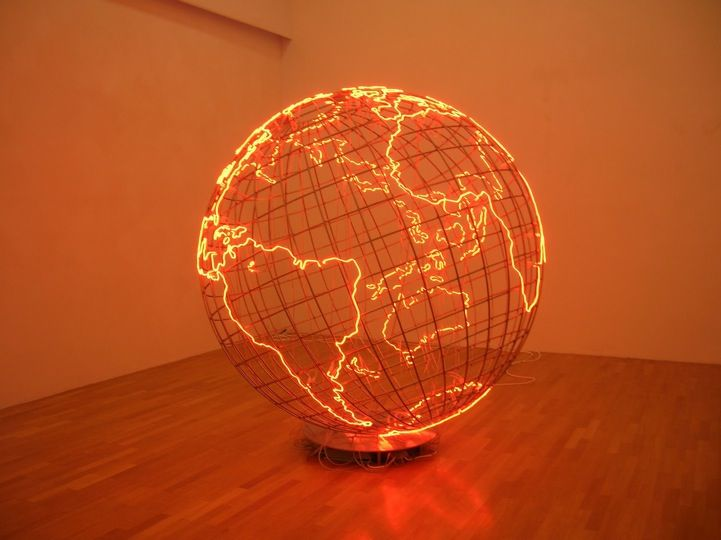 """In London and Berlin-based Palestinian artist Mona Hatoum's sculptural work titled Hot Spot, we are presented with a massive cage-like metallic globe radiating a crimson glow. In terms of global politics and news, a """"hot spot"""" generally refers to an area of conflict. Hatoum's piece highlights every land mass by outlining it in a neon red light that fills the room with an overwhelming scarlet hue. The structure seems to suggest that these neon contoured areas are the """"hot spots"""" of the world…"""