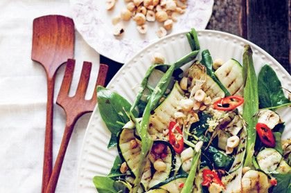 Grilled zucchini and spring onions with baby spinach and hazelnuts