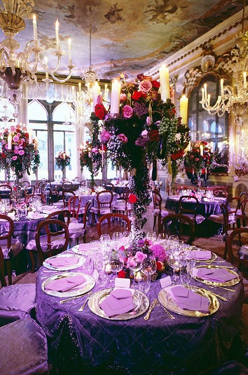 Candelabras overflowing with grapes, vines and roses top tables set   with violet linens and brilliant silver chargers.