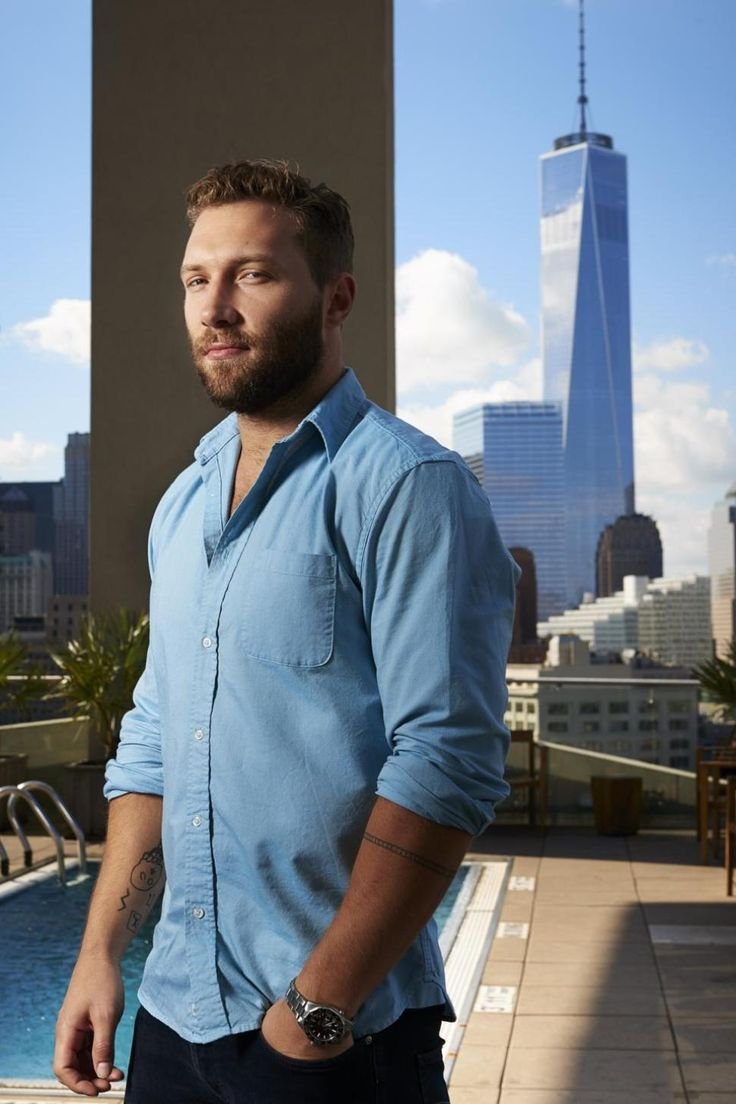 Actor Jai Courtney looks almost as gigantic as the One World Trade Center during a photo shoot at the JIMMY rooftop bar at the James Hotel.