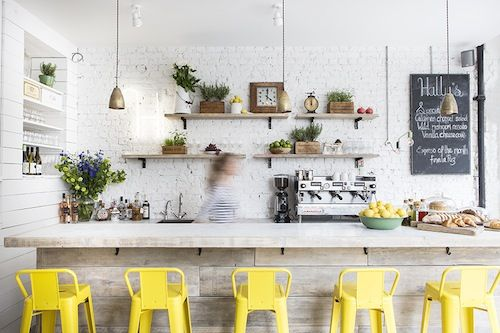 white brick, natural wood island, open wood shelves, pop of yellow tolix