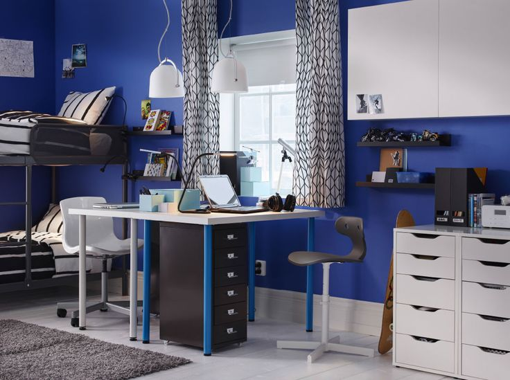A bedroom for twins furnished with two desks combined with drawer units on castors and a bunk bed.