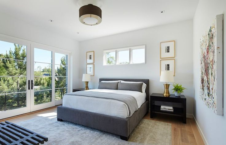 Weiß getünchten Wänden und Glastüren erfüllen dieses Master-Schlafzimmer in helle und luftige Atmosphäre.