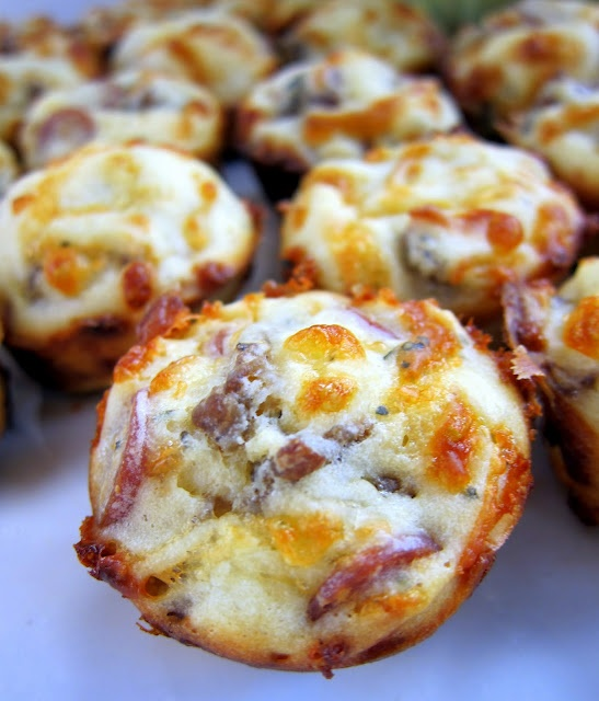 pizza puffs  3/4 cup flour   3/4 tsp baking powder   1/2 tsp garlic powder  3/4 cup whole milk   1 egg, lightly beaten   4 oz mozzarella cheese, shredded (about 1 cup)   2 oz mini turkey pepperoni, (about 1/2 cup)  4 oz low-fat sausage, cooked and crumbled   1/2 cup pizza sauce for dipping  375F 25min