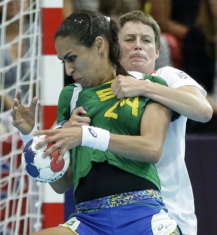 Lyn Byl of Great Britain, background, and Fabiana Diniz of Brazil challenge during their women's handball preliminary match at the 2012 Summer Olympics, Wednesday, Aug. 1, 2012, in London. (AP Photo/Matthias Schrader)