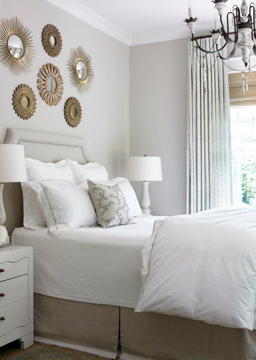 Amazing bedroom with gray walls paint color, gray linen headboard with silver nailhead trim, gray bed skirt, gallery of gold sunburst mirrors, white nightstands, marble lamps and gray curtains layered over bamboo roman shades.
