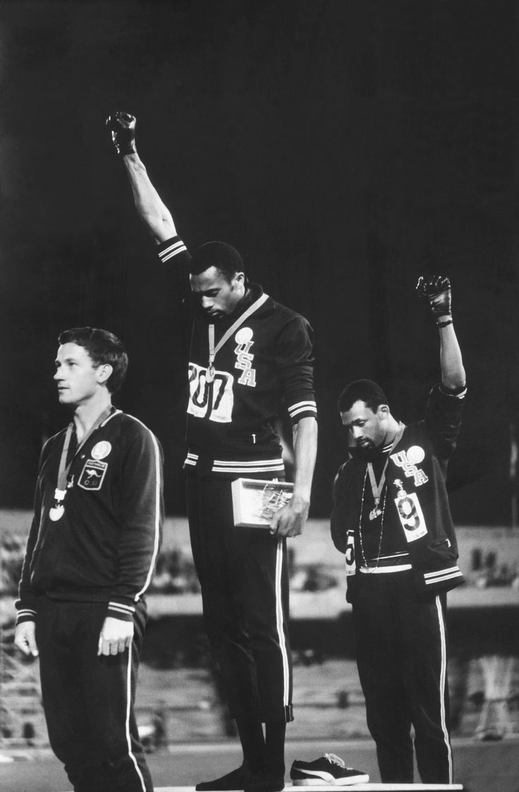 American track and field athletes Tommie Smith, center, and John Carlos, right, gold and bronze medal winners in the 200m, protest with the Black Power salute as they stand on the winner's podium at the Summer Olympic games, Mexico City, in 1968, photographed by John Dominis Photograph: Courtesy of John Dominis/Getty Images