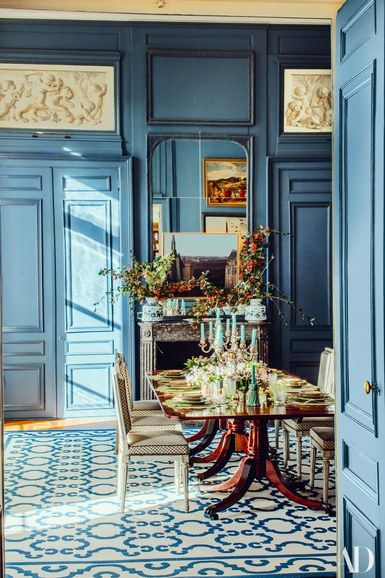 The dining room's 18th-century paneling—like all the apartment's boiserie—required painstaking restoration. Sauvage worked with designer Franz Potisek on the renovation. 19th-century english mahogany table; Louis XVI chairs covered in a Schumacher fabric; rug by Casa Lopez | archdigest.com