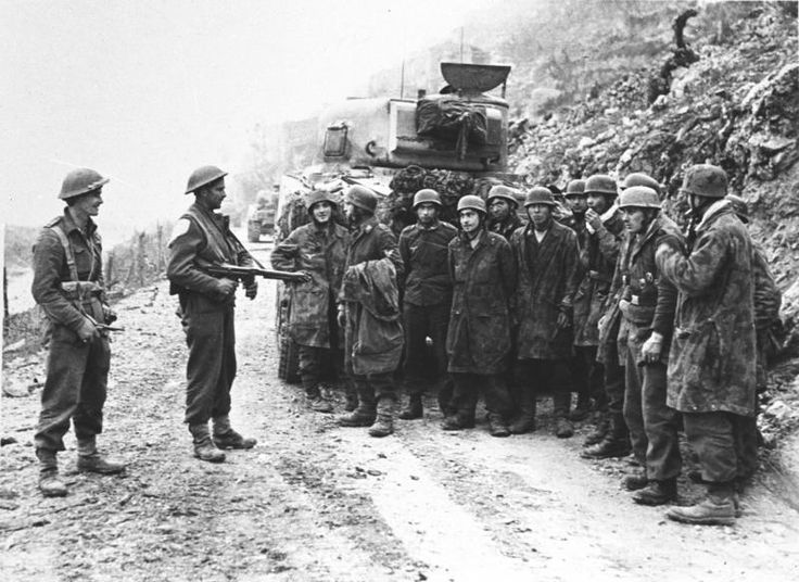 German prisoners captured by New Zealand troops are held beside a Sherman tank. After repeated unsuccessful assaults, the Allied offensive was again called off on 22 March.