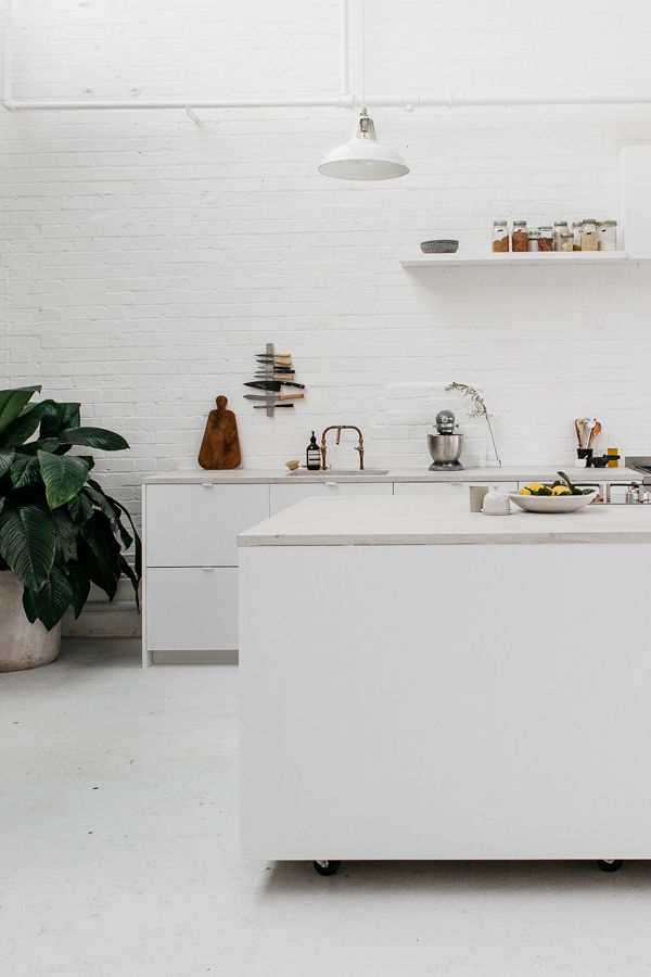 If you love bright white spaces, it doesn't get any more brilliant than this. Like floor to extremely high ceiling, light and bright brilliant. Even the concrete kitchen countertops feel airy. Copper hardware, a few well-placed cutting boards and a fiddle leaf add warmth. Now, I'll give that this isn't…