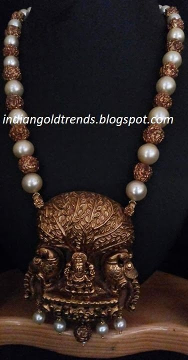 Beads necklace stuidded with pearls and gold rudraksha design beads which are attached to Kalapavruksham pendant strung with pearls.