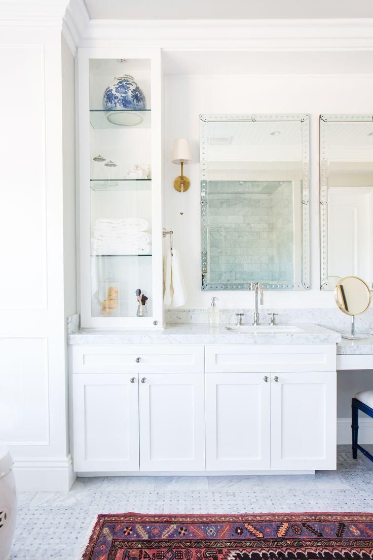 Traditional and classic white bathroom cabinetry, brass sconces with mini white lamp shades, and stunning gray and white carrara marble floors. Interior design and styling by Studio McGee.