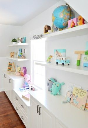 Add built in's and floating shelves around a window niche ... Young House Love .... White floating shelves under sloped ceiling filled with toys books and kids objects in a playroom